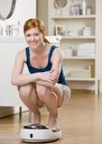 Glückliche Frau, die auf Skalen sich wiegt Stockfotografie