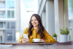 Glückliche Frau, die auf Smartphone am Stadtcafé simst Stockbild
