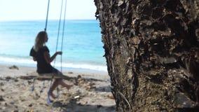 Gl?ckliche Frau, die auf Strandschwingen auf blauem der Meerwasser und Eidechse kriecht auf Baumstammhintergrund schwingt Service stock footage