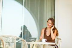Glückliche Frau, die auf Terrasse mit Tasse Kaffee sitzt Stockfoto