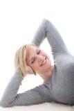 Glückliche Frau, die auf weißem Hintergrund liegt Stockbilder