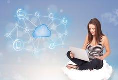 Glückliche Frau, die auf Wolke mit der Wolkendatenverarbeitung sitzt Lizenzfreies Stockfoto
