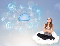 Glückliche Frau, die auf Wolke mit der Wolkendatenverarbeitung sitzt Stockfoto