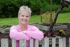 Glückliche Frau, die auf Zaun sich lehnt Stockfoto