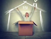 Glückliche Frau, die aus Kasten in ein neues Haus herauskommt lizenzfreie stockfotos