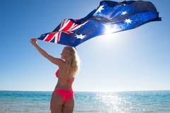Glückliche Frau, die australische Flagge am Strand fliegt Stockfotografie
