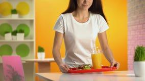 Glückliche Frau, die Behälter mit Salat und frischem Orangensaft auf Tabelle, Snackbar setzt stock footage