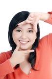 Glückliche Frau, die Bilderrahmen mit ihren Fingern zeigt Lizenzfreie Stockfotos