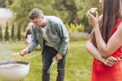 Glückliche Frau, die Brot während ihr Freund grillt shashliks isst stockfoto
