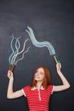 Glückliche Frau, die bunte Bleistifte hält und auf Tafelhintergrund zeichnet Stockbild
