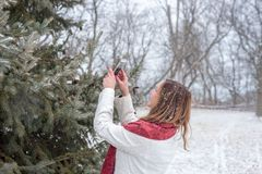 Glückliche Frau, die das Foto des Schnees fallend auf Kiefer mit sma macht Lizenzfreie Stockbilder