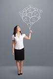 Glückliche Frau, die das lächelnde Ballonzeichnen hält Stockfoto