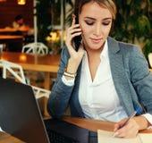 Glückliche Frau, die das Plaudern mit Mobile und GebrauchsLaptop-Computer verwendet Lizenzfreie Stockfotografie