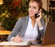 Glückliche Frau, die das Plaudern mit Mobile und GebrauchsLaptop-Computer verwendet Lizenzfreies Stockbild