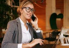Glückliche Frau, die das Plaudern mit Mobile und GebrauchsLaptop-Computer verwendet Lizenzfreie Stockfotos