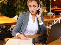 Glückliche Frau, die das Plaudern mit Mobile und GebrauchsLaptop-Computer verwendet Lizenzfreies Stockfoto