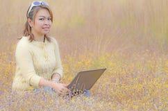 Glückliche Frau, die an dem Laptop im Freien arbeitet Stockfoto