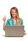 Glückliche Frau, die den Laptop gesetzt am Schreibtisch verwendet Stockbild