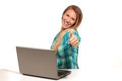 Glückliche Frau, die den Laptop gesetzt am Schreibtisch verwendet Stockbilder