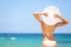 Glückliche Frau, die den Strand sich entspannt im Sommer genießt
