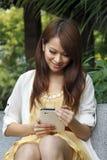 Glückliche Frau, die den Tablette PC im Freien betrachtet Stockbild