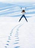 Glückliche Frau, die an den Winterbergen springt Stockfotografie
