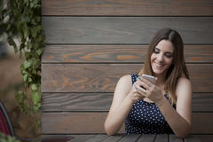 Glückliche Frau, die in der hölzernen Kaffeestube sitzt Lizenzfreies Stockbild