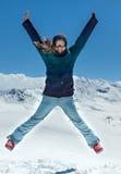 Glückliche Frau, die in die Berge springt Stockbild