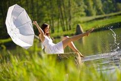 Glückliche Frau, die durch den See spritzt Wasser sitzt lizenzfreies stockbild