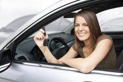 Glückliche Frau, die ein Auto mietet Lizenzfreie Stockfotografie