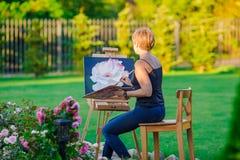 Glückliche Frau, die ein Bild auf einem Gestell auf a malt Lizenzfreie Stockfotos