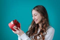 Glückliche Frau, die ein Geschenk in Form von Herzen hält Lizenzfreie Stockfotos