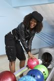 Glückliche Frau, die eine Bowlingkugel aufhebt Lizenzfreies Stockbild