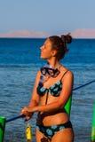 Glückliche Frau, die eine Maske im Meer, zusammen mit einer Kamera trägt Lizenzfreies Stockbild