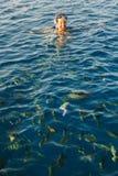 Glückliche Frau, die eine Maske im Meer, zusammen mit einer Kamera trägt Lizenzfreie Stockbilder