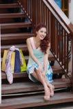 Glückliche Frau, die eine Pause mit Einkaufstaschen beim Sitzen auf t macht Stockbilder