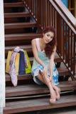 Glückliche Frau, die eine Pause mit Einkaufstaschen beim Sitzen auf t macht Stockfoto