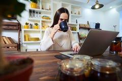 Glückliche Frau, die eine Tasse Tee bei der Anwendung des Laptops sitzt ind trinkt Stockbild