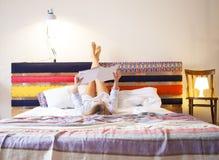 Glückliche Frau, die eine Zeitschrift auf dem Bett liest Stockbilder