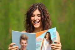 Glückliche Frau, die eine Zeitschrift liest stockbilder