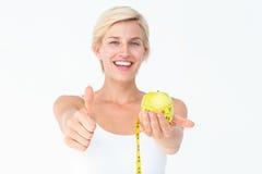 Glückliche Frau, die einen Apfel mit den Daumen oben hält Stockfotografie