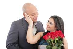 Glückliche Frau, die einen Blumenstrauß von roten Rosen ihres Liebhabers empfängt Lizenzfreie Stockbilder