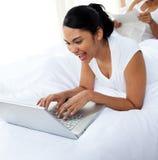 Glückliche Frau, die einen Laptop liegt auf dem Bett verwendet Lizenzfreies Stockbild