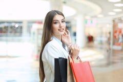 Glückliche Frau, die Einkaufstaschen hält und im Einkaufszentrum lächelt stockfoto