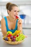 Glückliche Frau, die Erdbeere in der Küche isst Lizenzfreies Stockfoto