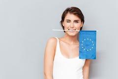 Glückliche Frau, die europäische Flagge in den Zähnen und im Blinzeln hält Stockfoto