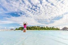 Glückliche Frau, die für Freude im Ozean auf Tropeninsel in Malediven springt Lizenzfreie Stockbilder