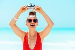 Glückliche Frau, die Fotos mit Retro- Fotokamera auf Seeküste macht lizenzfreie stockfotos
