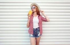Glückliche Frau, die frischen Orangensaft im Sommerrundenstrohhut, kariertes Hemd, kurze Hosen auf weißer Wand genießt lizenzfreie stockbilder