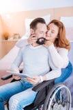 Glückliche Frau, die gelähmten Mann umarmt Lizenzfreie Stockbilder